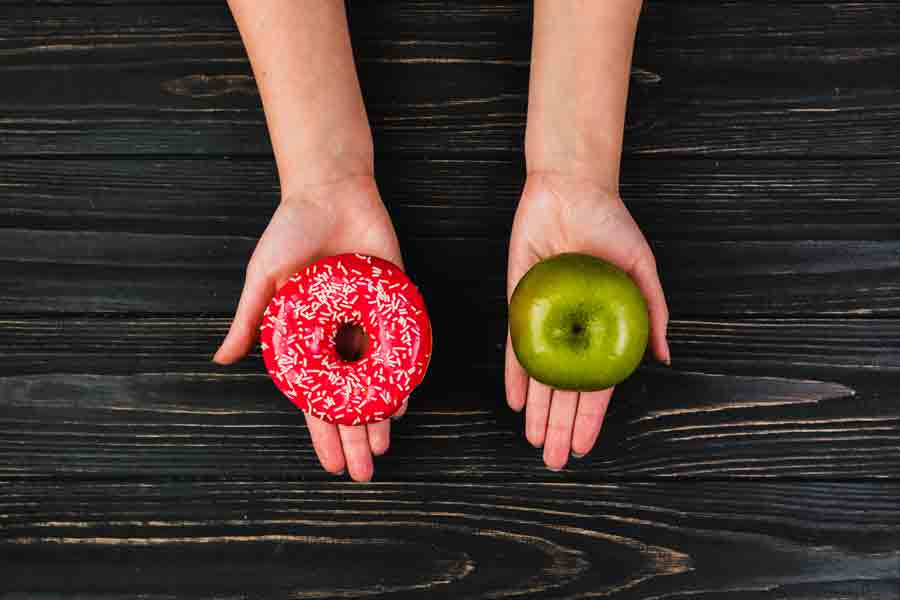 A crop hands holding a donut and apple.