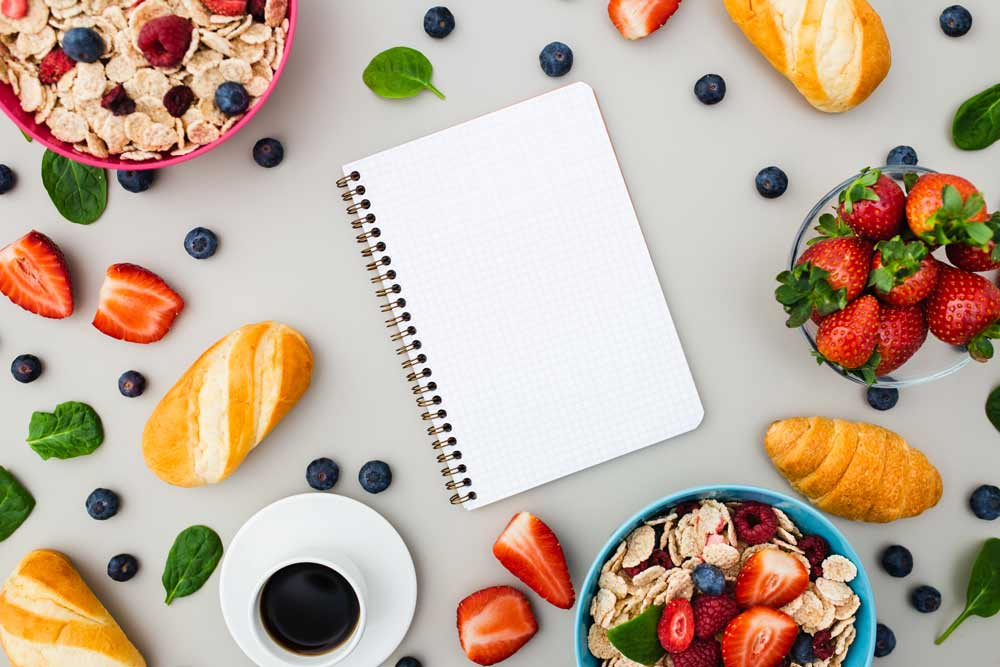 A diary surrounded by healthy foods.