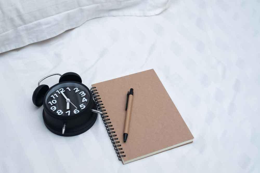Dream diary or notebook and vintage alarm clock on bed in bedroom.